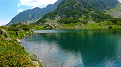 Beautiful view of a lake in the Pirin mountain, Bulgaria, with a fisherman Stock Footage