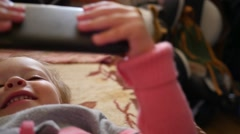 Little kid girl watch a smart phone lying on a couch in bright morning sun haze - stock footage