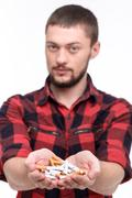 Cheerful young guy is quitting bad habit Stock Photos
