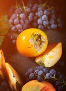 Stock Photo of Persimmon and grapes still life.Autumn season food photo. Yellow toning appli