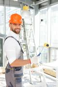 Handsome young painter is working at house - stock photo