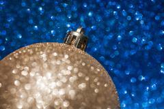 Golden christmas ball on blue glitter background - stock photo