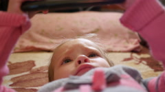 Little kid girl watch cartoons via smart phone display lying on a couch - stock footage