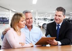 Senior couple with car dealer. - stock photo