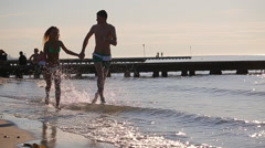 Happy couple is running along the shore Stock Footage
