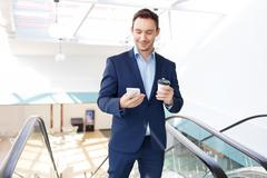 White collar worker glances at his smartphone - stock photo