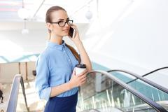 Female office worker is speaking on the phone - stock photo