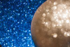 Golden christmas ball on glitter background - stock photo