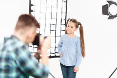 Little model poses when being photographed - stock photo
