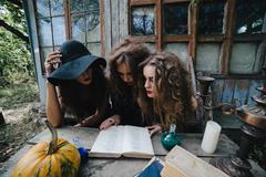 Three vintage witches perform magic ritual - stock photo