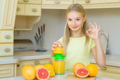 Child with oranges. Girl squeezed fresh orange juice and showing Ok Stock Photos