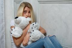 Depressed girl sitting on the floor Stock Photos