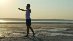 Young man warming up for a jog on the bank of the river early in the morning Stock Footage