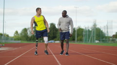 4K Disabled athlete with prosthetic leg working out with trainer @ running track - stock footage