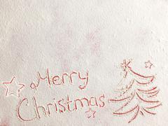 Merry Christmas written on white snow - stock photo