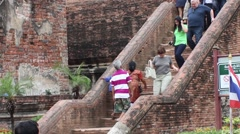 Tourists descend the stone stairs to the ancient Buddhist buildings Stock Footage