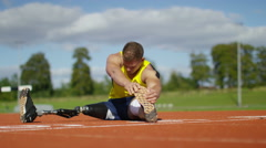 4K Disabled athlete with prosthetic leg warming up at running track - stock footage