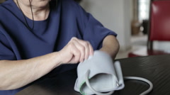Woman putting blood pressure arm band Stock Footage