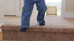 Cute little boy walking down the stairs in a home - stock footage