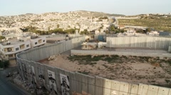 West Bank separation barrier wall wide shot, Bethlehem outskirts behind - stock footage