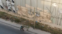 West Bank separation barrier, Israel, street sweeper walks past wall, high shot - stock footage