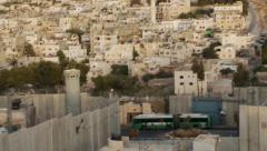 West Bank separation barrier wall, tilt up to Jewish settlement near Bethlehem - stock footage