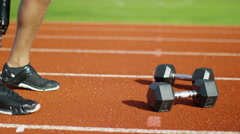 4K Disabled athlete with prosthetic leg working out with weights @ running track - stock footage
