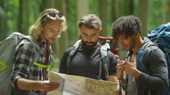 4K Friends hiking in the woods looking at map and trying to find their way Stock Footage