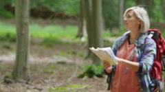 4K Young woman hiking in the woods, looking at map and trying to find her way Stock Footage