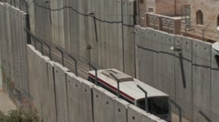 Israeli West Bank Barrier wall, bus takes Jews to Rachel's tomb holy place - stock footage