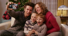 Loving Family Kissing Children Pulling Faces On Christmas Eve Stock Footage