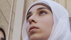 Palestinian young girl wearing al-amira looks up Stock Footage