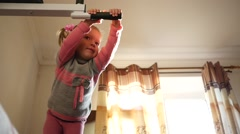 Sport little kid girl at home in morning swaying on the horizontal bar Stock Footage