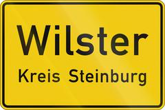 A German regulatory road sign: Beginning of urban area of Wilster, district S - stock illustration