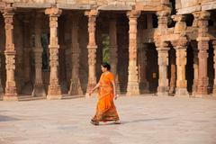 Indian woman walking through courtyard of Quwwat-Ul-Islam mosque, Qutub Minar Stock Photos
