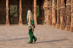 Indian woman walking through courtyard of Quwwat-Ul-Islam mosque, Qutub Minar - stock photo
