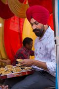 Indian man giving away rice at Guru Nanak Gurpurab celebration during communi - stock photo