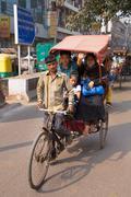 Cycle rickshaw carrying passengers in New Delhi, India - stock photo