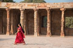 Indian woman walking through courtyard of Quwwat-Ul-Islam mosque, Qutub Minar - stock photo