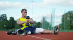 4K Disabled athlete with prosthetic leg working out with weights @ running track Stock Footage
