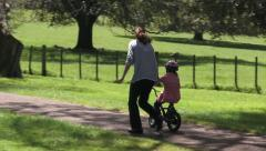 Parent teaching a child to how to ride bicycle without stabilisers in the park Stock Footage