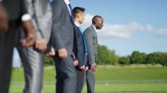 4K Competitive businessmen at running track line up at starting line before race Stock Footage