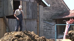 Worker on a trailer flattens the manure Stock Footage