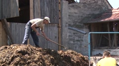 Worker and forklift loading manure Stock Footage