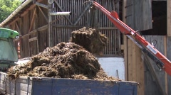 Loading manure onto the tractor trailer Stock Footage