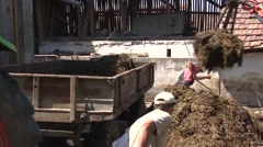 Piling up livestock manure onto trailer Stock Footage