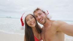 Christmas couple taking selfie on beach holidays wearing santa hat having fun Stock Footage