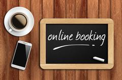 Coffee, phone  and chalkboard with word online booking Stock Photos