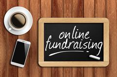 Coffee, phone  and chalkboard with word online fundraising Stock Photos