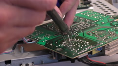 Engineer soldering parts onto electronic circuit board Stock Footage